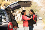 stock-photo-28700406-mother-and-daughter-embracing-behind-car-on-college-campus