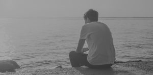 Young man sitting by water. Suicide is the 10th leading cause of death in the U.S.