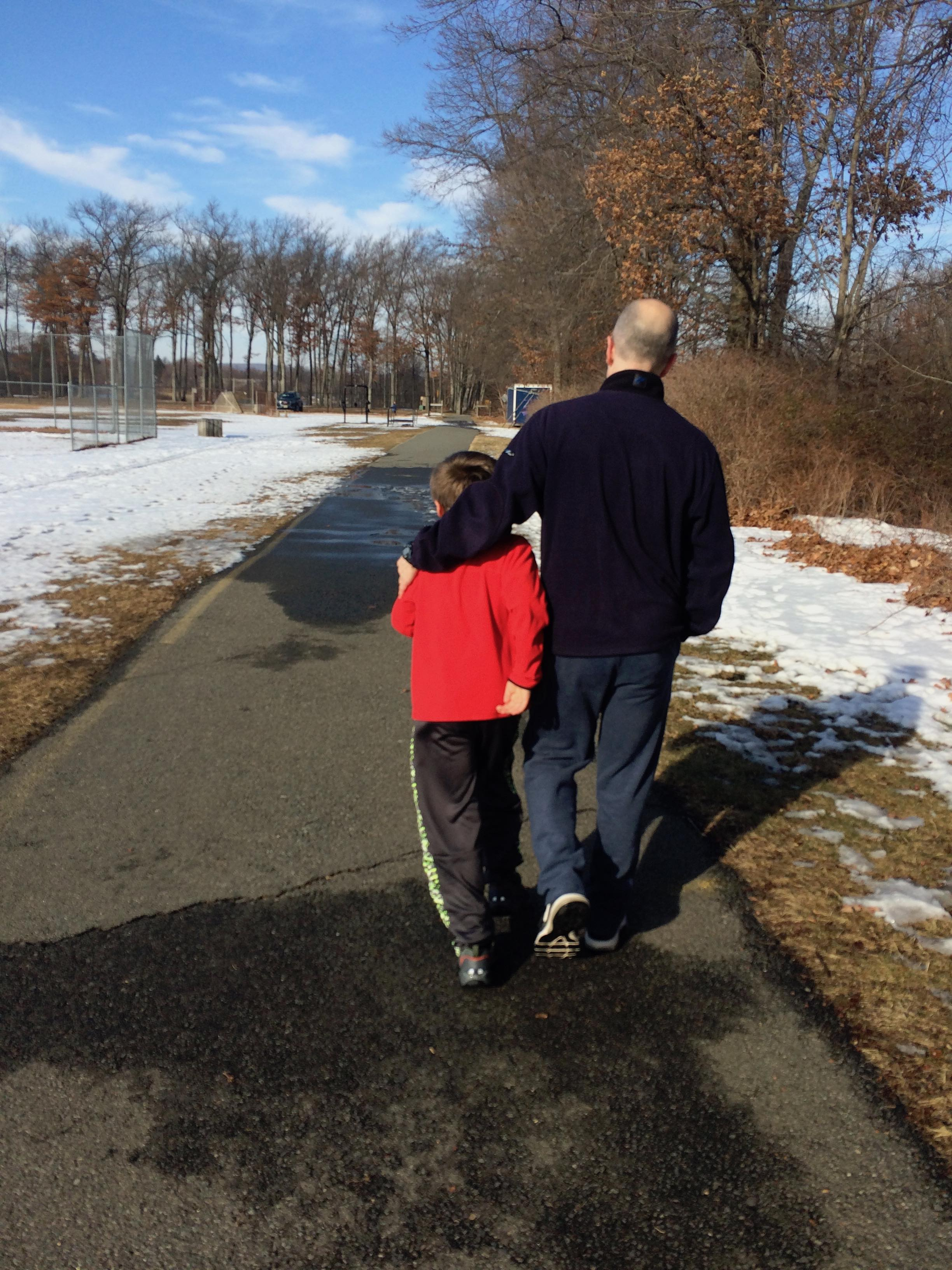 Dad and son walking together. It's important for parents to talk to their children about bad news.
