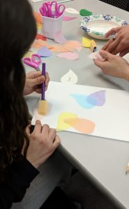 A girl making a decoupage pinwheel on canvas.