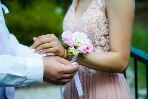 Teenage boy placing a corsage on his prom date's wrist.