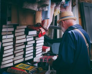 Older man perusing books.