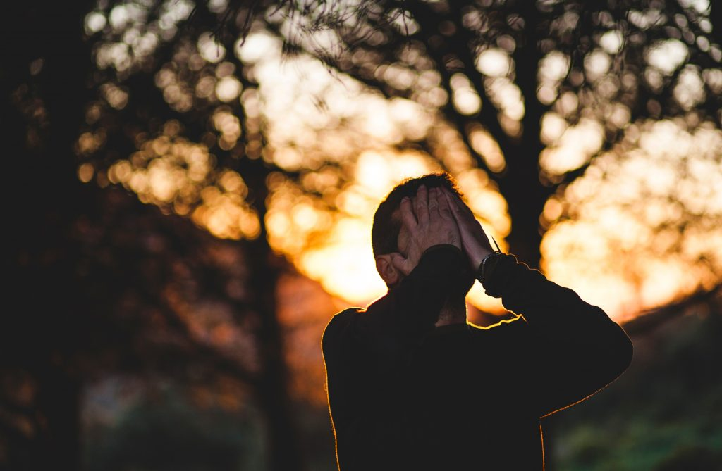 Man with hands over his face. Behind him, it appears the sun is setting behind trees Photo by Francisco Moreno on Unsplash.