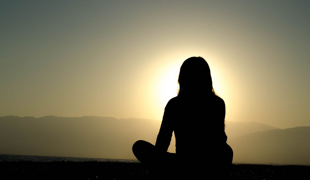 Mindfulness Meditation can help alleviate anxiety. Photo shows a woman meditation at sunrise.