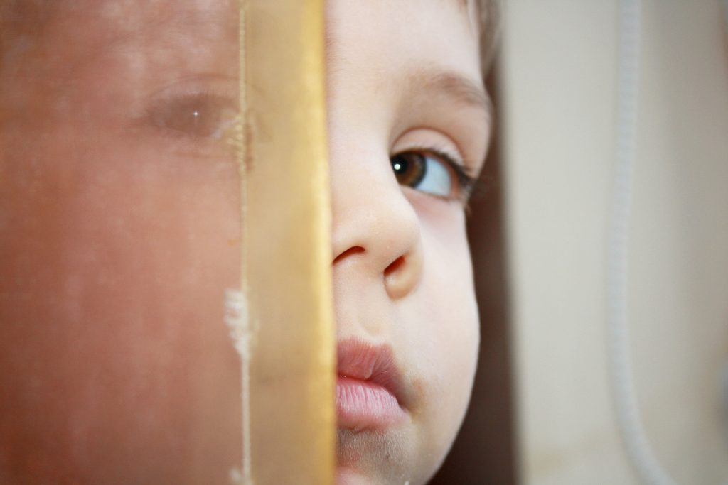 Small child peeking out from sheer curtain. The COVID-19 pandemic is expected to increase incidents of domestic violence and child abuse and neglect.