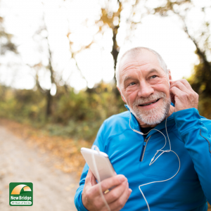 Healthy Aging Month. Man listening to a smartphone during a break from exercising