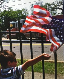 Practicing compassion/boy waving flag at Memorial Day parade