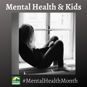 Older child or teen sitting by a window. Learn the signs of mental illness during Mental Health Month.