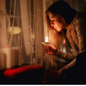 Coping skills can help you manage this holiday season. Photo shows woman holding a lighted candle near a window.