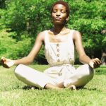 Practice self-care with meditation. Photo shows woman meditating outdoors.
