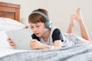 Boy using the internet on iPad lying on the bed. Photo by Emily Wade on Unsplash.com